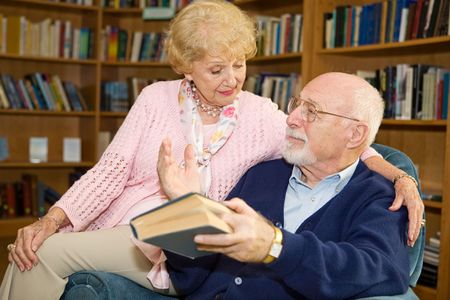 Senior man and woman reading together and discussing. Stock Photo - 2834907