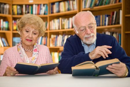 Senior couple together reading at the library. Stock Photo - 2834904