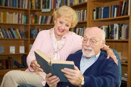Senior couple enjoying a good book together in the library.   Stock Photo - 2834906