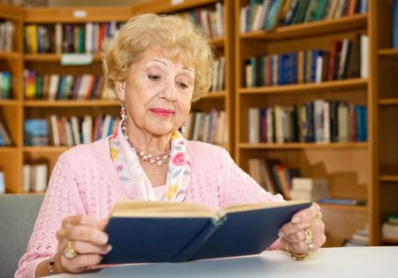 Beautiful senior student reading a book at the library.   Stock Photo - 2834891