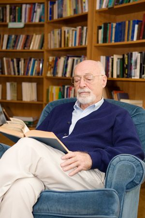 Intelligent senior man reading in the library. Stock Photo - 2834892
