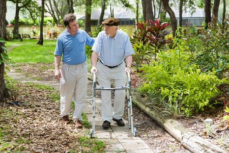 elderly care: Elderly father and adult son out for a walk in the park.