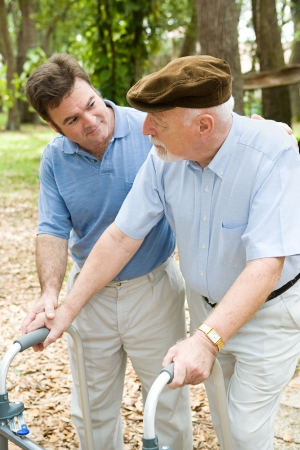Adult son caring for his aging father who is confined to a walker.   Stock Photo - 2839801