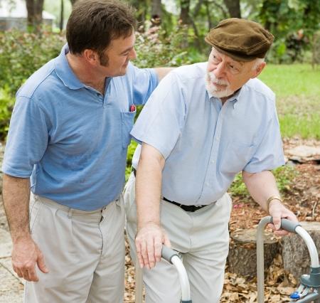 preocupacion: Hijo del adulto hacia fuera para una caminata con su padre, que tiene enfermedad de los alzheimers. Foto de archivo