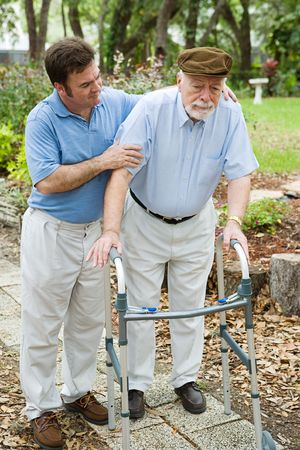 Senior man looks sad as he struggles to walk using a walker.  His adult son is helping him.   photo