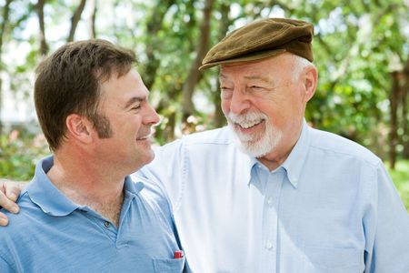 companionship: Senior father and adult son laughing together in the park.
