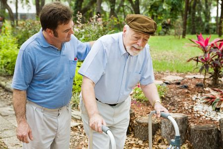 dementia: Senior man struggling to us a walker.  His adult son is helping him.