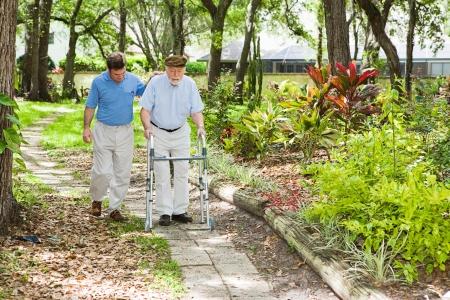 marcheur: Fils dadulte aidant son p�re � employer un marcheur dans le parc.