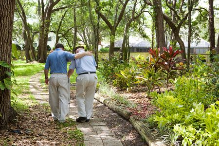 dementia: View from behind of an adult son walking with his senior father in the park.