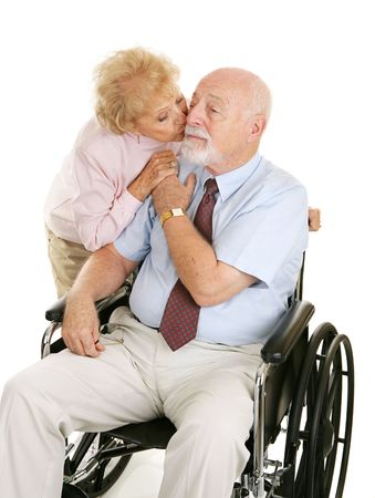 Senior man in wheelchair receiving a kiss from his devoted wife.  Isolated on white.