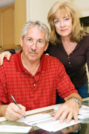 Mature couple looking worried as they try to pay the bills.  Focus on the husband.   photo