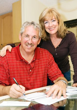 50: Beautiful mature couple going over bills together and smiling.