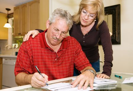 Mature couple in financial trouble is filling out a loan application.   Фото со стока