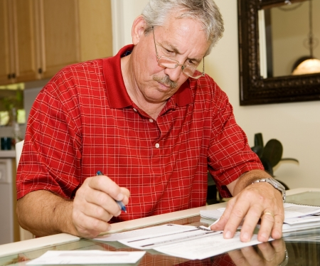 paying: Handsome mature man signing papers beside a stack of bills.
