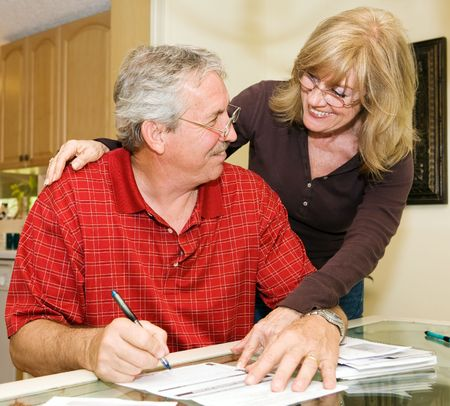 Mature couple happy about paying off their debts. Stock Photo - 2870388