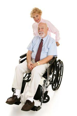 persona en silla de ruedas: Hombre mayor en un sill�n de ruedas con su esposa cari�osa que lo empuja. Cuerpo completo en blanco.