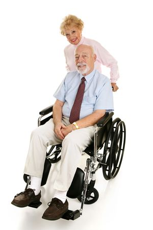 Senior man in a wheelchair with his loving wife pushing him.  Full body on white.   Stockfoto