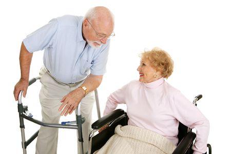 gehhilfe: Senior Mann in walker Flirt mit einem hohen Dame in einem Rollstuhl. Isoliert auf Wei�.