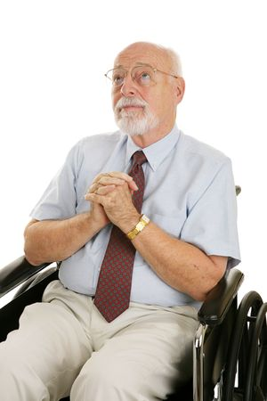 Senior man in a wheelchair with his hands folded in prayer.  Isolated on white. photo