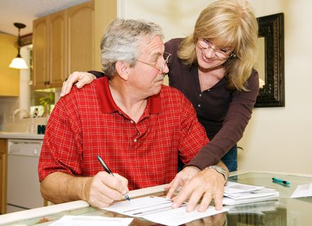 Senior woman persuading her husband to sign paperwork.  He looks skeptical.   photo