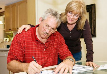 Mature couple at home signing paperwork together.   photo