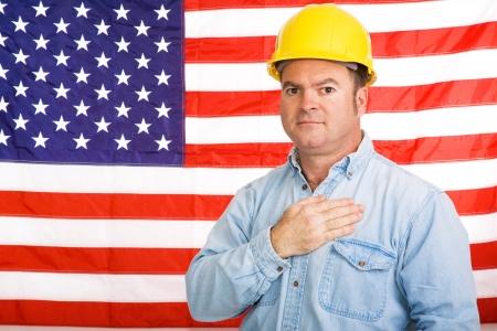 Patriótico trabajador americano con su mano sobre su corazón delante de los EE.UU. bandera. Fotografiado delante de bandera, no imagen.  Foto de archivo