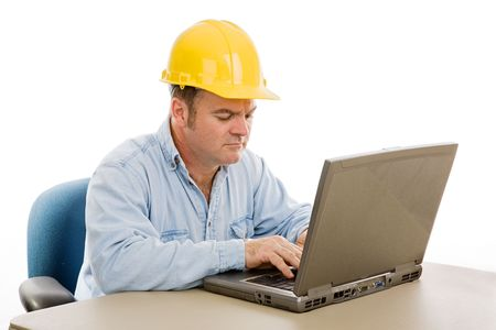 architect tools: Construction contractor in the office on his laptop.  Isolated on white.