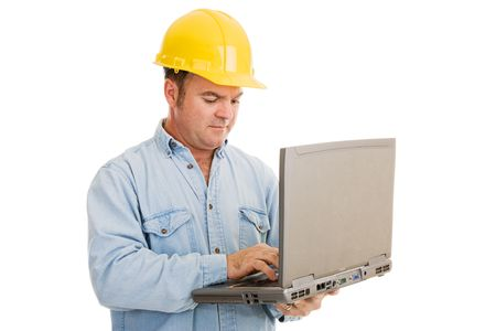 Construction engineer using his laptop computer on the job.  Isolated on white.   photo