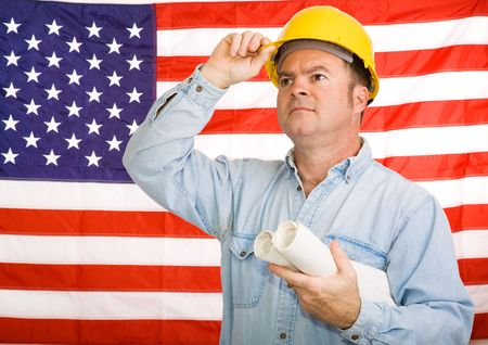 tipping: Construction worker with blueprints tipping his hardhat to the American flag.  Photographed in front of the flag, not a composite image.