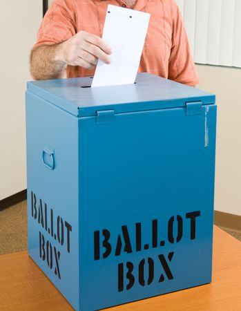 box: Closeup of a mans hand placing his ballot in the box.