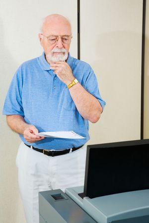 Homme aîné le jour d'élection, confus par la machine de vote de nouveau balayage optique.