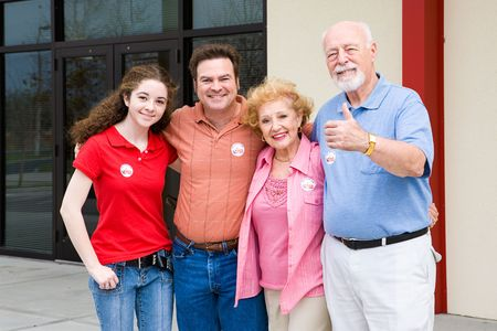 Family standing outside their polling place wearing I Voted stickers.  (stickers are generic ones, not trademarked)