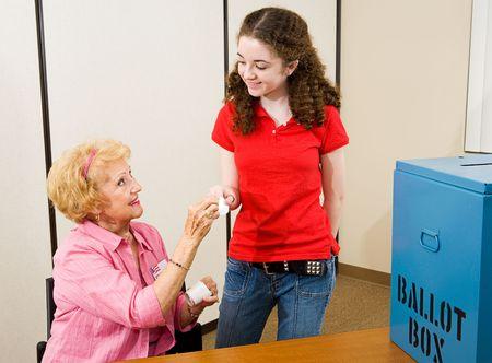 głosowało: Starszy kobiety podające I Zagłosowano naklejki do młodych po raz pierwszy wyborców. Zdjęcie Seryjne