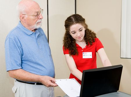 Teen volunteer helping senior voter use the new equipment on election day.