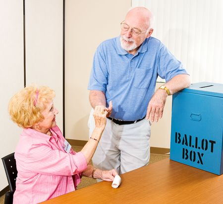 electronic voting: Senior man collects his I Voted sticker from a friendly volunteer.