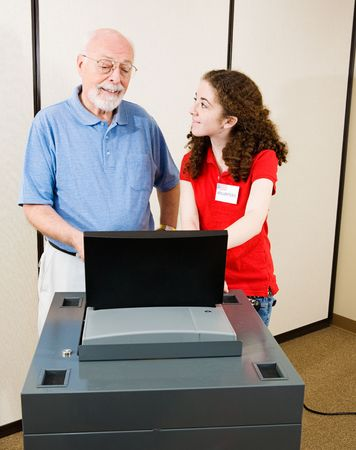 Volunteer explains new optical scan voting machine to a senior on election day.
