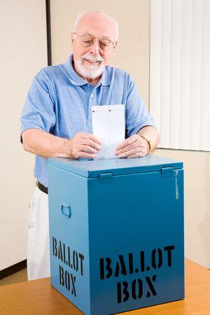 voting: Handsome senior man casting his ballot at the polls.
