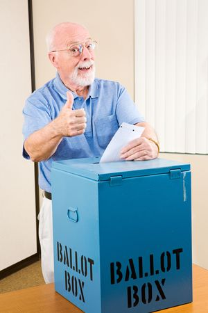 voting: Senior man giving the thumbs-up sign as he casts his ballot.