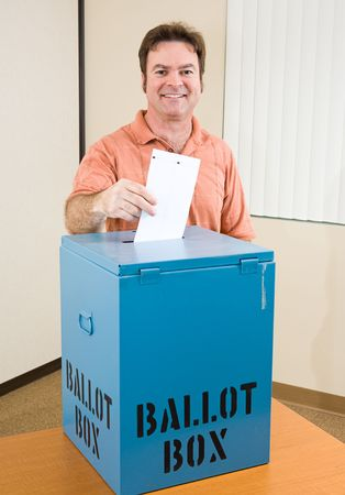 voting: Middle aged caucasian man casting his ballot in the election.