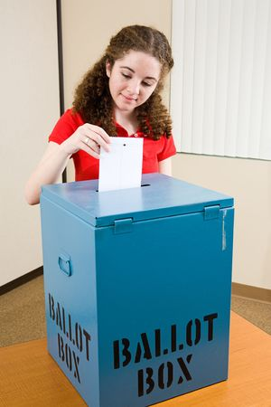voting: Young first time voter dropping her ballot in the box at the polling place. Stock Photo