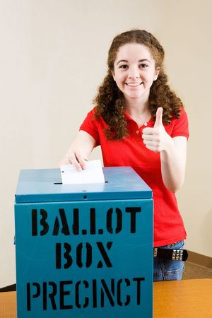 voter: Young first time voter casting her ballot and giving a thumbs-up sign.   Stock Photo