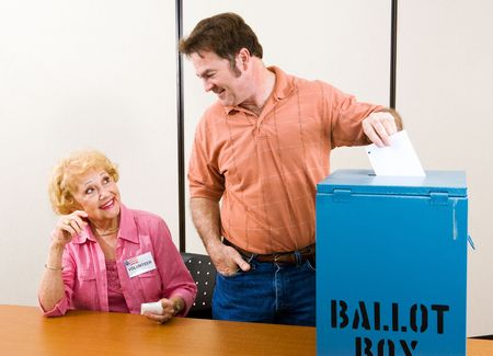 voter: Male suburban voter casting his ballot while an election volunteer looks on.   Stock Photo