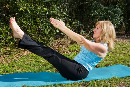 Amazingly fit and beautiful mature woman doing an advanced pilates move.   photo