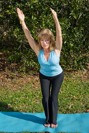 Beautiful sixty year old woman doing the chair pose in yoga, outdoors in a natural setting. photo