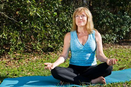 room for text: Beautiful mature woman doing yoga in a lovely natural setting.  Room for text.