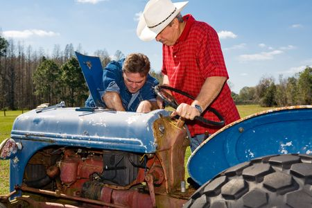 checkered polo shirt: Farmer and ranch hand work on repairing the old tractor together.