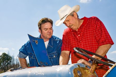 checkered polo shirt: Rancher and ranch hand working together to repair the tractor.
