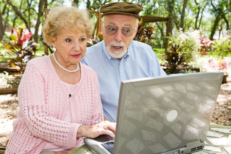 Senior couple using their laptop computer in lovely outdoor setting.  Hes shocked by what he sees online. photo