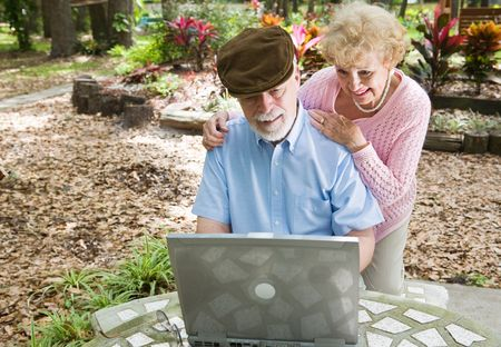 room for text: Senior couple on the computer outdoors in a natural setting.  Horizontal view with room for text.