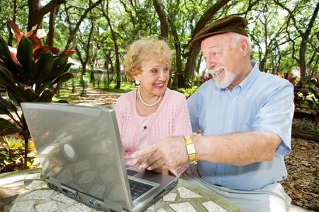 Senior couple on their laptop computer in a beautiful, natural setting.   photo